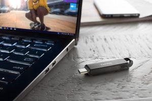 SanDisk Ultra 32GB USB 3.1 TYPE-C Flash Drive 150 MB/s naast een laptop, uitgeschoven.